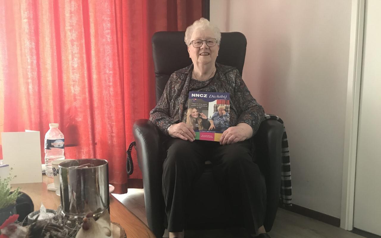 Grietje Kroezen op haar kamer. Op de voorpagina van het NNCZ-blad dat zij in haar hand heeft zag zij Jo-an voor het eerst.