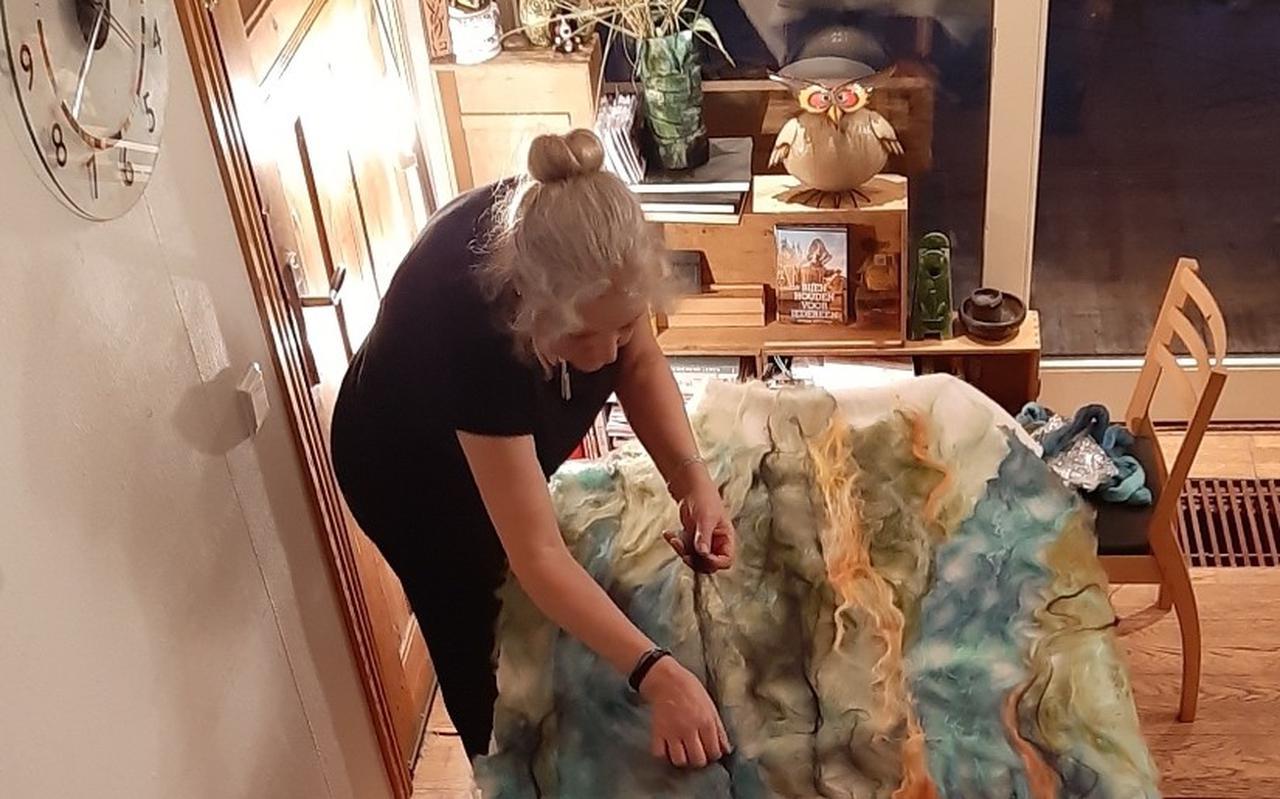 Anita Zwart aan het werk met haar kunstwerk van vilt.