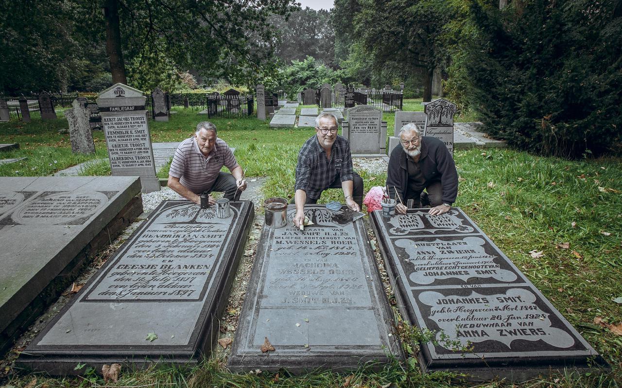 Jan Bouwmeester (links), Roelof Mulder en Henk Boer (rechts) leggen de laatste hand aan een grafsteen. In totaal hebben ze 160 graven opgeknapt.