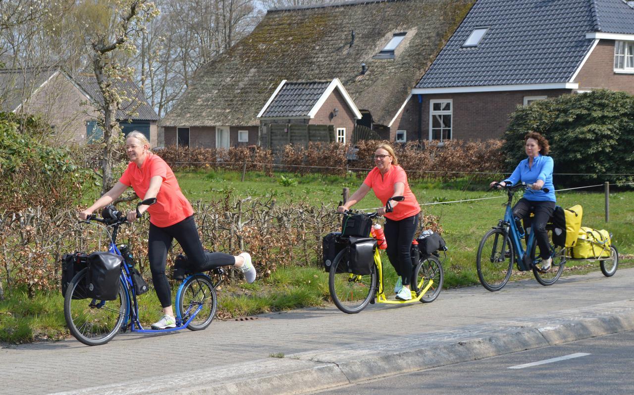 Daar gaan de dames over het fietspad in Koekange: voorop Erna Bijsterbosch, gevolgd door Albi Popken en daarachter op de eBike Aukje Kuyer, die haar medereizigers straks 2500 kilometer bij probeert te houden.