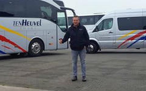Ronnie ten Heuvel bij een paar van zijn taxibussen.